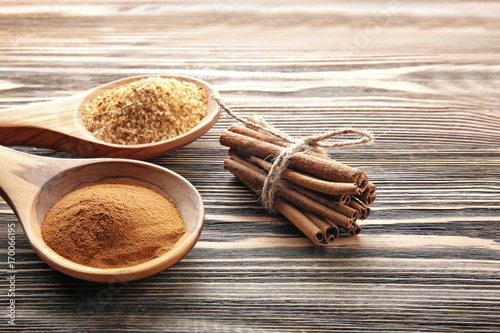 Fotobehang Kruiden 2 Composition with cinnamon sugar and powder in spoons on wooden background