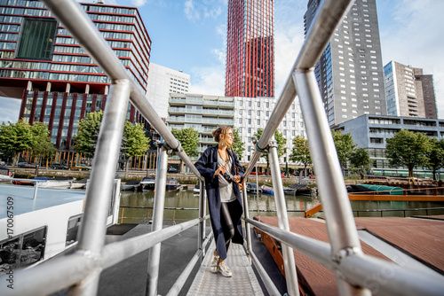 Foto op Plexiglas Rotterdam Young woman traveling at the modern harbor with skyscrapers on the background in Rotterdam city