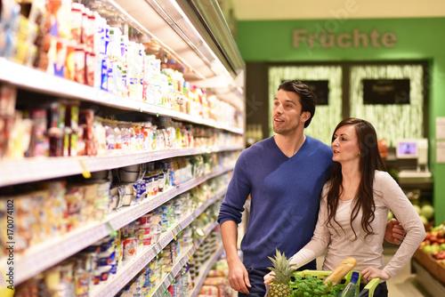 young couple shopping at the supermarket // junges Paar beim Einkauf am Regal im Supermarkt