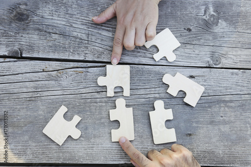 Business partnership or teamwork concept with a business people presenting a matching puzzle piece as they cooperate on finding an answer and solution, close up of their hands Poster