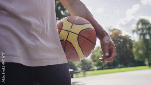 Aluminium Basketbal Unseen basketball player holding a ball on an outdoor court