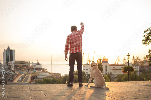 happy young male with dog watching sunrise with rised fist
