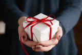 young female hands holding gift box with red ribbon