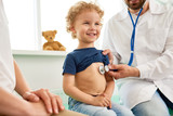 Portrait of adorable little boy visiting doctor, looking brave and smiling, holding  while pediatrician listening to heartbeat with stethoscope - 170126713