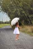 Dancing young girl in summer rain