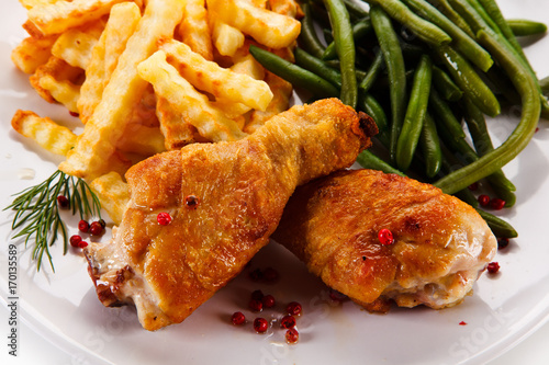 Grilled drumsticks with french fries and vegetables  - 170135589