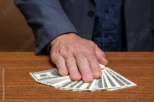 The man puts his hand over the money lying on the table