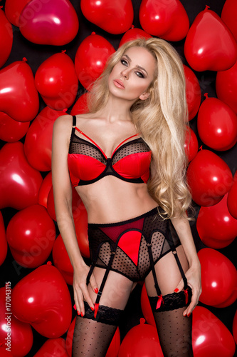 beautiful sexy blonde model woman with long hair standing on the background of red hearts for Valentine's Day balloons in red and black lace erotic lingerie and stockings tempting looks into the lens - 170143115