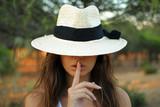 chica joven con sobrero y con un dedo en sus labios indicando silencio - 170145314