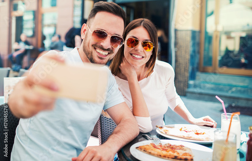 Fotobehang Pizzeria Beautiful young couple sitting in the cafe and eating pizza. Consumerism, food, lifestyle concept