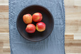 Four red apples in a wooden bowl on a wooden table. The view from the top.