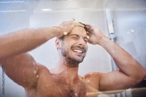 Cheerful well-built handsome young man laughing while in the shower