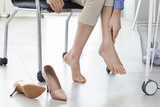 Young woman suffering from foot pain in office - 170157122