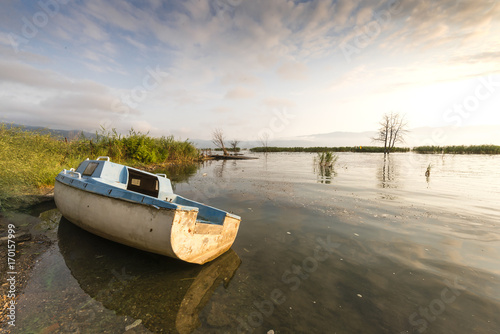 Fotobehang Schip Image of an abandoned boat on the lake in morning sunlight