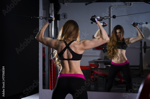Wall mural Fitness woman workout with training machine in gym