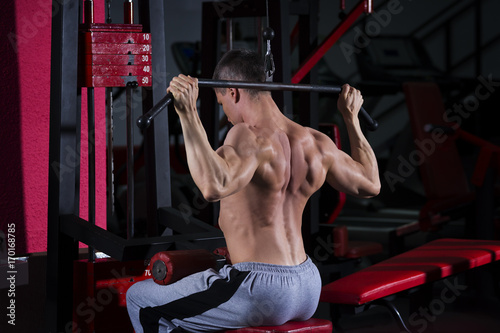 Wall mural Bodybuilder workout on trainer in gym, muscular body