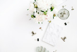 Flat lay home office desk. Woman workspace with white peony flowers bouquet, accessories, marble diary on white background. Top view feminine background.