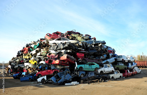 Old damaged cars on the junkyard waiting for recycling