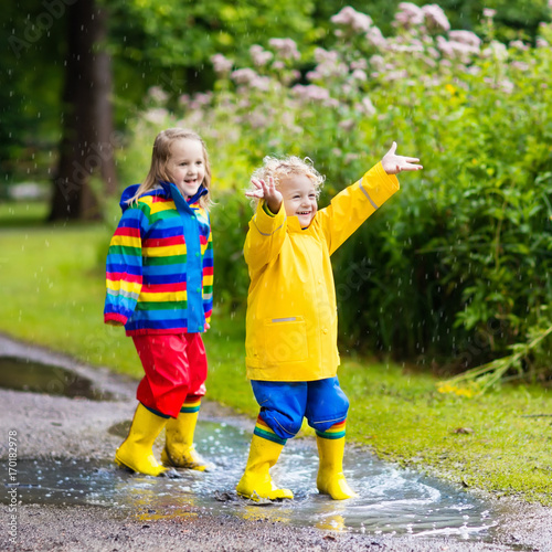 Kids play in rain and puddle in autumn Poster