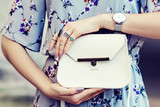 Close up photo of white leather bag in hands of fashionable woman pising in street. Model wearing silvery wrist watch, a lot of rings. Elegant outfit. Female fashion concept