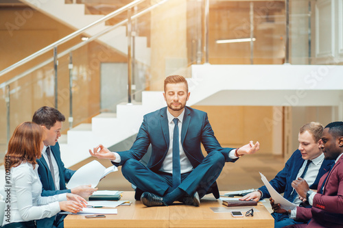 Businessman wearing a suit doing Yoga on the table and other businessmans angry