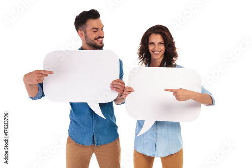 casual couple holding speech bubbles pointing to each other