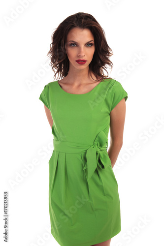 young woman in green dress holding hands at her back