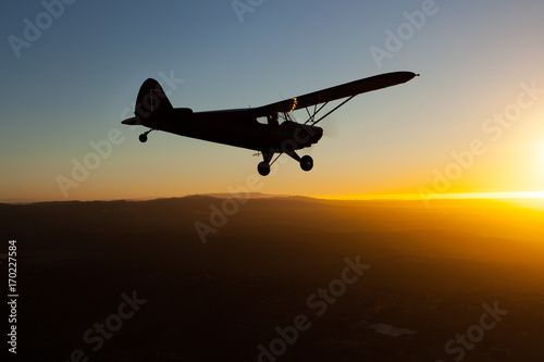 Plakat Romantic airborne evening: beautiful silhouette of a plane flying towards the se