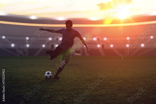 Soccer player is kicking a ball to the net in stadium at sunset. Poster