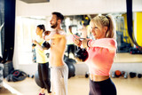 Athletic fit people are doing shoulder workout with the kettlebell.