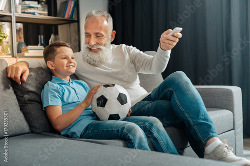 Man turning air conditioning on while watching football with grandson