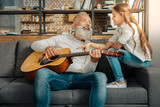 Grandfather chatting with granddaughter while holding guitar - 170235542