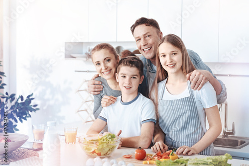 Radiant family posing for camera while cooking Poster