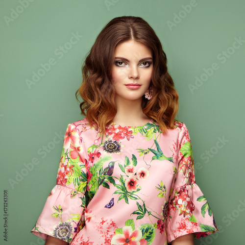 Fotobehang Kapsalon Brunette young woman in floral spring summer dress. Girl posing on a green background. Summer floral outfit. Stylish wavy hairstyle. Fashion photo. Brunette lady
