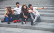 Group of friends sitting together on stairs and talking, city background