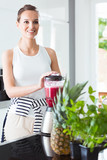 Fit woman making delicious smoothie
