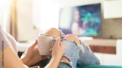 Beautiful young woman relaxing on the sofa at home, watching tv and enjoying coffee