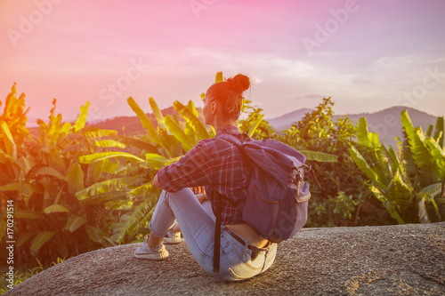 Fotobehang Lichtroze Hipster young girl with backpack enjoying sunset on peak mountain. Tourist traveler on background valley landscape view mockup. Toned. Instagram filter