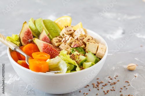 Foto op Canvas Boeddha buddha bowl with tofu, figs, avocado and other vegetables, tahini filled