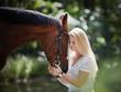junge blonde Frau mit ihrem Pferd