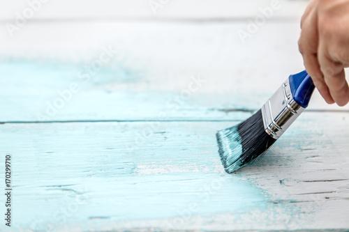 Nahaufnahme, Pinsel malt über Holz, Kreidefarbe in Weiß und Hellblau