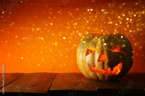 Halloween Pumpkin on wooden table in front of spooky dark background. Jack o lantern