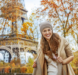 Portrait of smiling young elegant woman near Eiffel tower, Paris