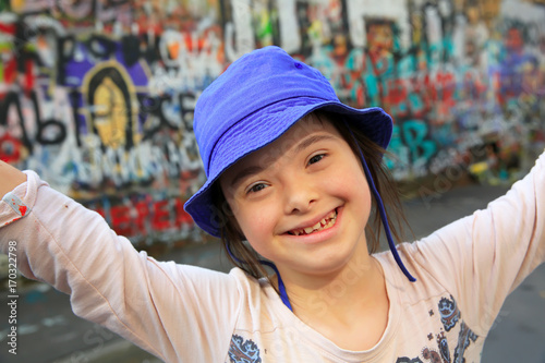 Fotobehang Graffiti Cute smiling down syndrome girl on the background of the graffiti wall