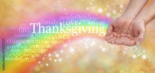 Celebrate Thanksgiving - Male hands cupped with a bright rainbow flowing from behind and a THANKSGIVING word cloud arcing across on a warm golden sparkling background with copy space