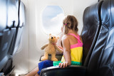 Child in airplane. Flight with kids. Family flying.