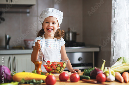 Healthy eating. Happy child girl prepares  vegetable salad in kitchen