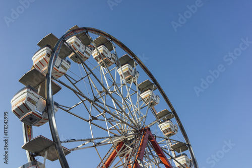 Fotobehang Amusementspark Ferris wheel against a blue sky at a carnival