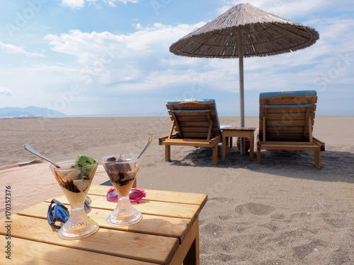 Two lounges and two ice cream on the beach © shvets_tetiana