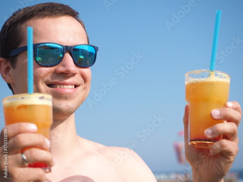Happy man with two glasses of healthy fresh juice on the beach © shvets_tetiana